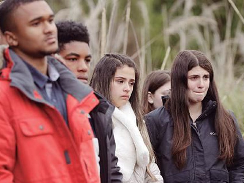 Students from the Marjory Stoneman Douglas High School in Parkland, Florida, react after planting trees at Halswell Quarry Park Conservation Area on the outskirts of Christchurch, New Zealand. (AP)