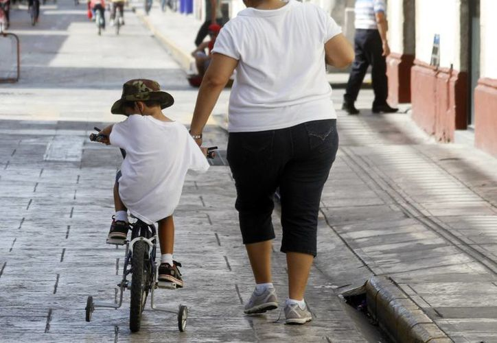 El estilo de vida, es un factor importante para prevenir los infartos al corazón. Imagen de una mujer y un niño en calles del centro de la ciudad. (Milenio Novedades)