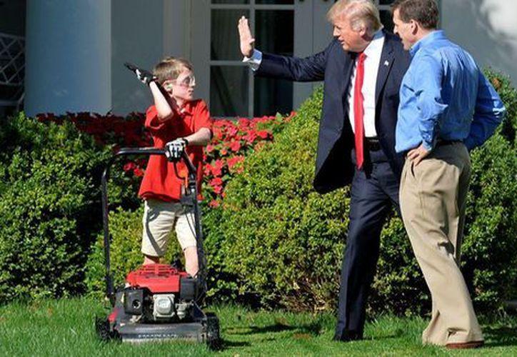 Donald Trump dejó que un niño de 11 años cortara el pasto de la Casa Blanca. (AFP).