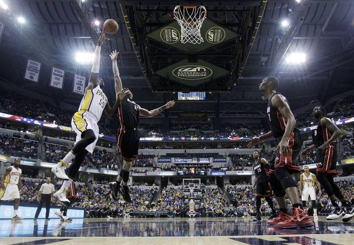 Roy Hibbert (55), de Pacers de Indiana, lanza la pelota frente a Chris Andersen (11), de Heat, durante el partido de la NBA. (Foto: AP)