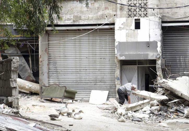 Imagen de archivo que muestra a un hombre mientras busca entre los escombros junto a la entrada de un edificio en el campo de refugiados de Al Yarmuk, en el sur de Damasco, Siria. (Archivo/EFE)