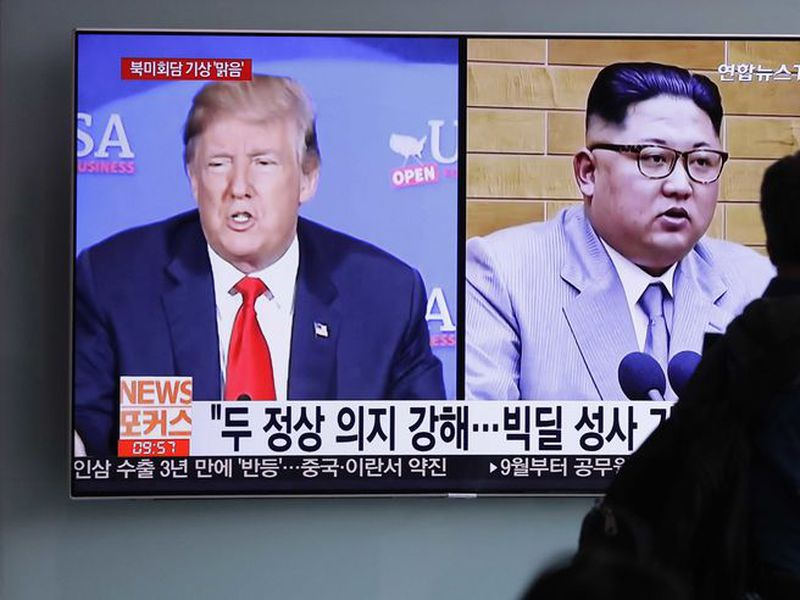 A man watches a TV screen showing file footage of U.S. President Donald Trump, left, and North Korean leader Kim Jong Un. (AP)