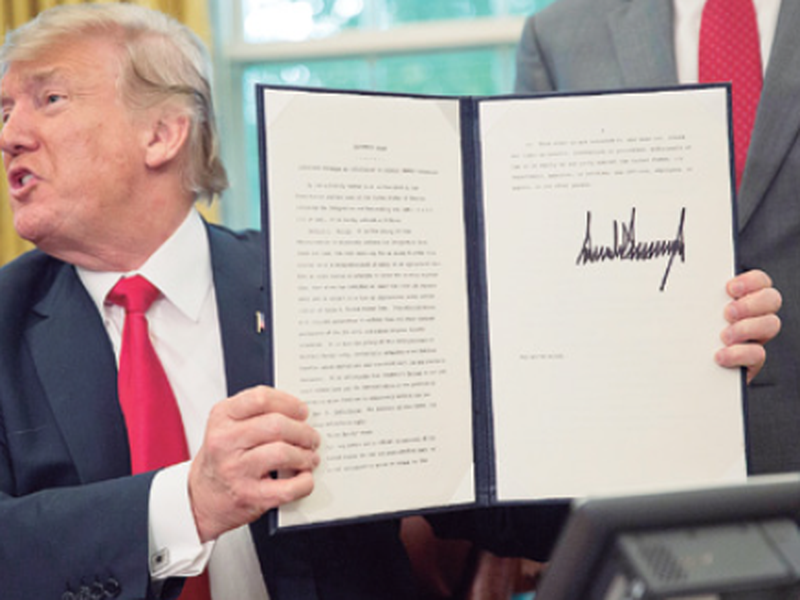 PresiDenT Donald trump holds up the executive order he signed to end family separations at the border. (AP)