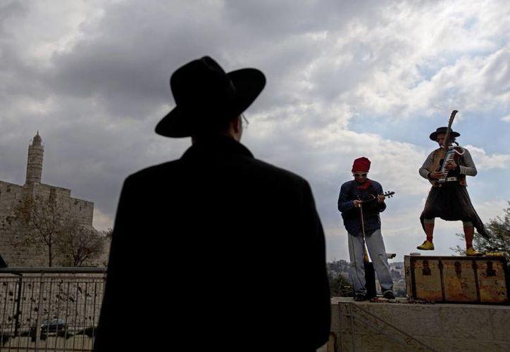 Fotografía de archivo del 6 de febrero de 2014 de un judío ultraortodoxo observando a músicos callejeros cerca de la Torre de Davi, en Jerusalén. (Agencias)