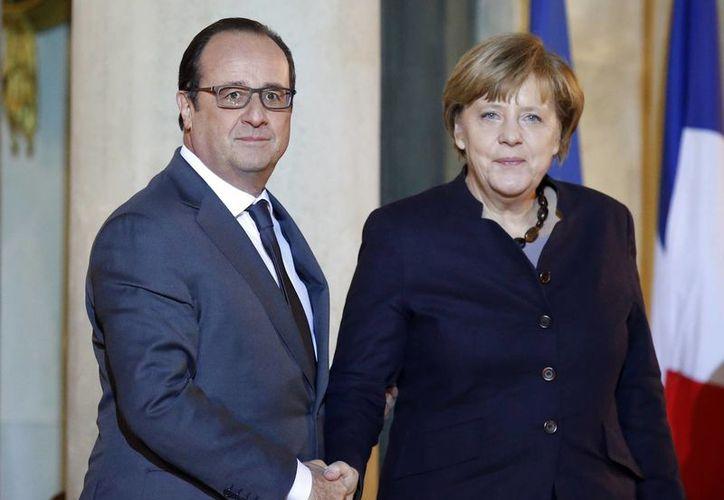 El presidente francés, Francois Hollande, da la bienvenida a la canciller alemana, Angela Merkel, a su llegada en el Palacio del Elíseo, en París. (Agencias)