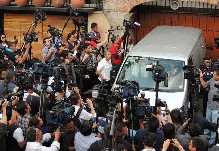 Un grupo de periodistas toma imágenes del ingreso de la carroza fúnebre a la casa del escritor Gabriel García Márquez en la Ciudad de México. (EFE)