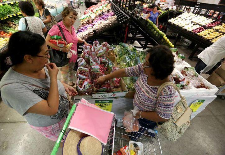 A pesar del triunfo de Donald Trump en las elecciones presidenciales de EU y la incertidumbre económica generada en México, el PIB creció 2.4 por ciento. Imagen de contexto de dos mujeres en un supermercado de Mérida. (Archivo/Notimex)