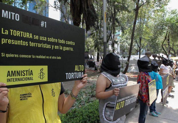 Integrantes de Amnistía Internacional con el rostro cubierto protestan a las afueras de la PGR en la Ciudad de México. (Archivo/EFE)