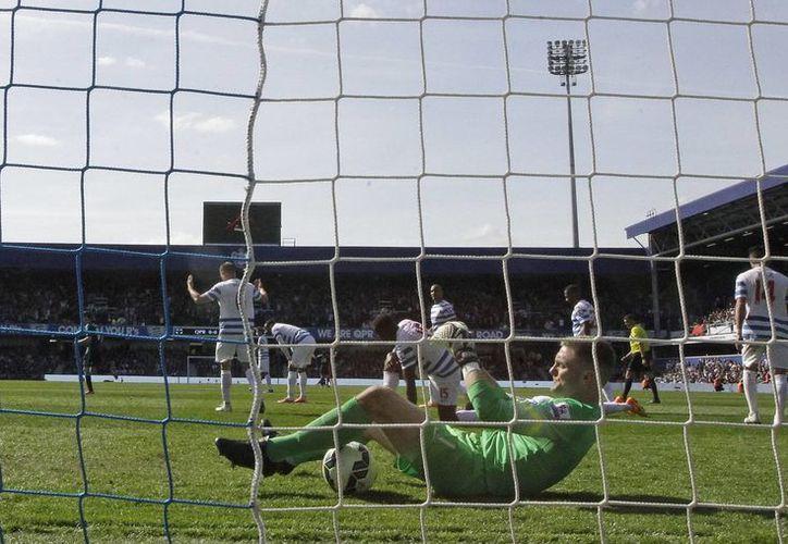 El arquero Robert Green, del Queens Park Rangers, yace en el pasto luego de que su meta fue perforada por Cesc Fábregas para dar el triunfo por 1-0 al Chelsea en la Liga Premier. (Foto: AP)