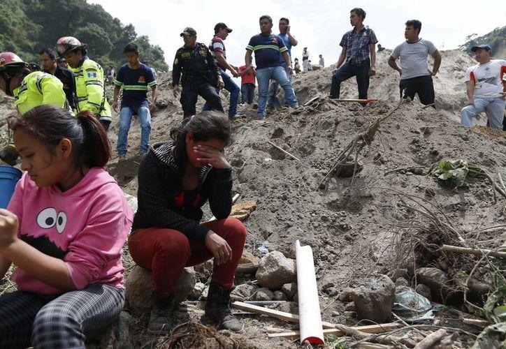 Los residentes de Santa Catarina Pinula observan a los cuerpos de rescate trabajar después del alud de lodo que afectó a la población. Las fuertes lluvias provocaron una ladera a colapsar en decenas de casas. (Foto AP/Moises Castillo)