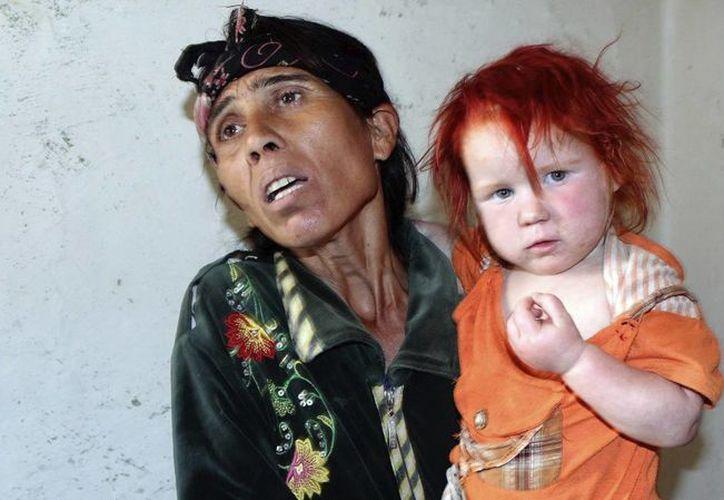 La supuesta madre de la niña conocida como el 'Ángel rubio', carga a otra de sus hijas en su domicilio de Nikolaevo, Bulgaria. (EFE)
