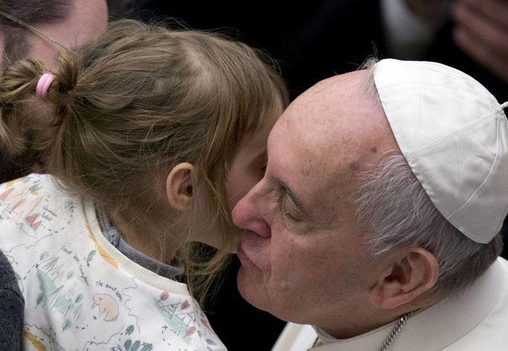 Francisco besa a una niña durante su audiencia general semanal, en el Vaticano. (Agencias)