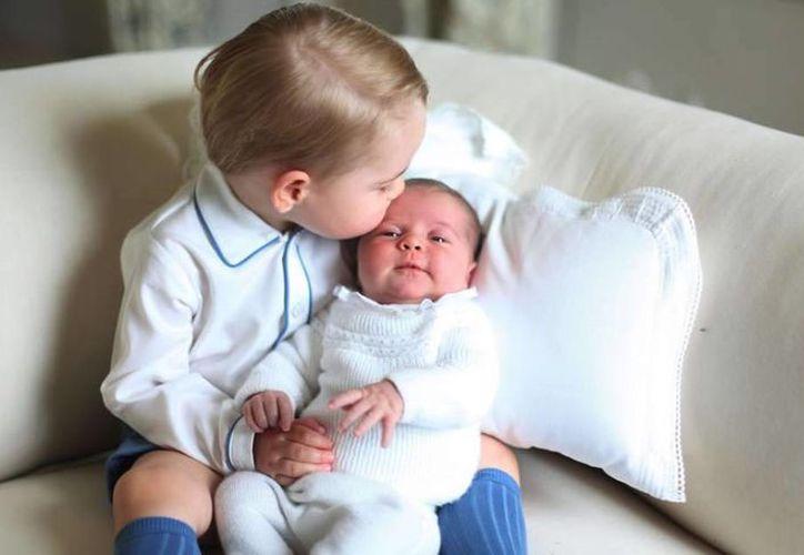 El príncipe inglés George besa a su hermanita, la princesa Charlotte. La foto fue tomada por la madre de ambos, la duquesa Kate Midleton. (laprensa.hn)