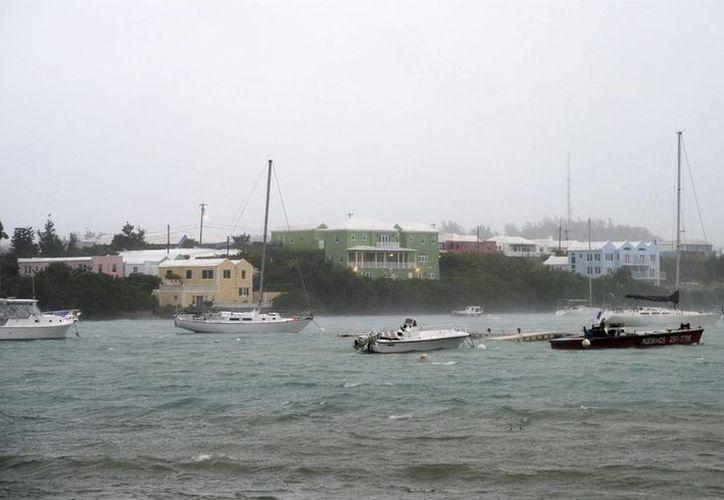 Fuertes lluvias y vientos sacuden embarcaciones en la Bahía Mullet en St. Georges, Bermudas, este jueves, 13 de octubre del 2016. Puertas y ventanas comenzaron a 'volar' al acercarse el huracán Nicole a este territorio británico, como una peligrosa tormenta de Categoría 3. (AP Foto/Mark Tatem)