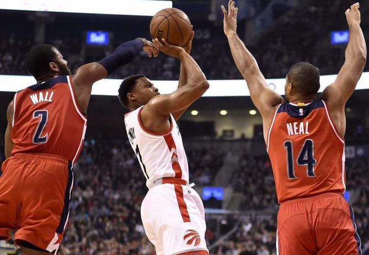 Kyle Lowry (centro) encabezó el triunfo de los Raptors de Toronto de este martes con 29 puntos. (Imágenes de AP)