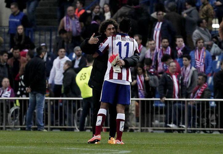 Guillermo Ochoa (de frente), que podría salir del club Málaga, saluda a su compatriota mexicano Raúl Jiménez al término de un partido entre Málaga y Atlético de Madrid. (Foto de archivo de Notimex)