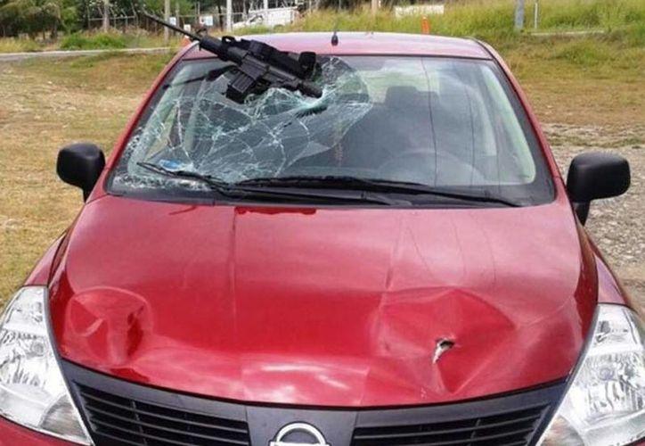 El arma del delincuente quedó incrustada en el parabrisas del carro. (Foto tomada de Excelsior/El Mañana de Reynosa)