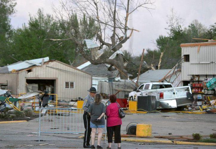 Un policía habla con residentes de la localidad de Baxter Springs, Kansas, cuyas casas sufrieron daños por el tornado. (Agencias)