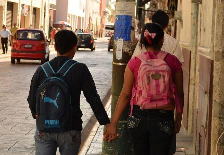 En México, las mujeres que tuvieron un embarazo en la adolescencia terminan su periodo reproductivo hasta con tres hijos más que las mujeres que iniciaron su maternidad después de los 19 años. Imagen de una pareja adolescentes. (Jorge Acosta/SIPSE)