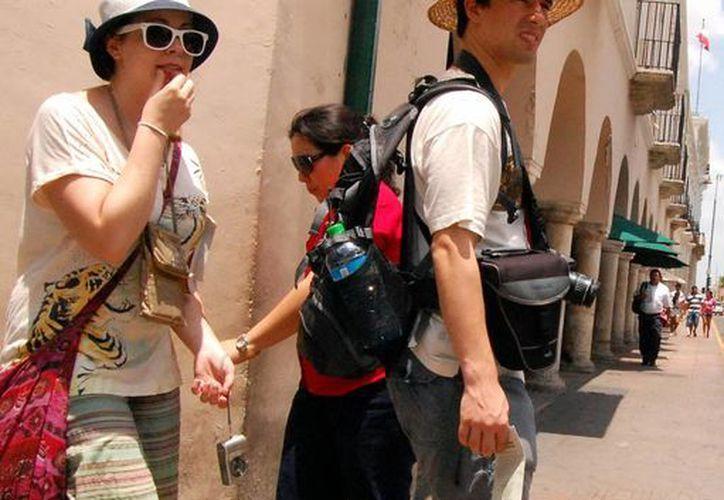 Para las vacaciones de verano se espera que sea una temporada turística positiva. Imagen de dos turistas en el Centro histórico de Mérida. (Milenio Novedades)