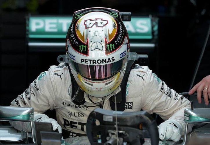El piloto Lewis Hamilton, que tuvo una complicada mañana, pero una buena tarde, abandona su auto durante un ensayo rumbo al Gran Premio de Malasia de Fórmula Uno. (Foto: AP)