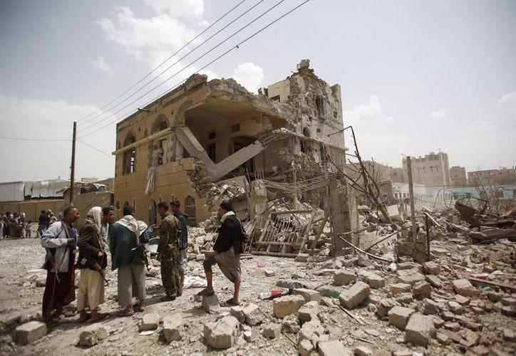 Imagen de los rebeldes chiíes que se reúnen en las casas destruidas por un ataque aéreo saudita en Saná, Yemen, el pasado viernes.  (Foto AP/Hani Mohammed)
