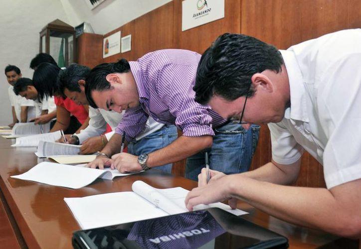 Los ahora titulares firman actas validados por la responsable de la Auditoría Superior del Estado. (Cortesía/SIPSE)
