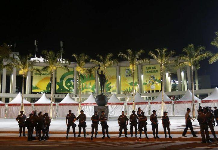 Un grupo de policías custodia las inmediaciones del estadio Maracaná durante una protesta para exigir mejores servicios públicos. (EFE/Archivo)