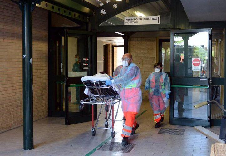 Una mujer de nacionalidad extranjera es sacada en camilla de una sala de urgencias de un centro de salud para ser trasladada a un hospital de la localidad de Civitanova Marche en la provincia de Ancona, Italia, por un posible caso de ébola. (EFE)