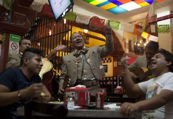 El mariachi Jaime Gamez canta para los clientes Pedro Fuentes (izq), y Manuel Cortés, al interior del restaurante bar Salón Tenampa en la Plaza Garibaldi de la Ciudad de México. (Agencias)