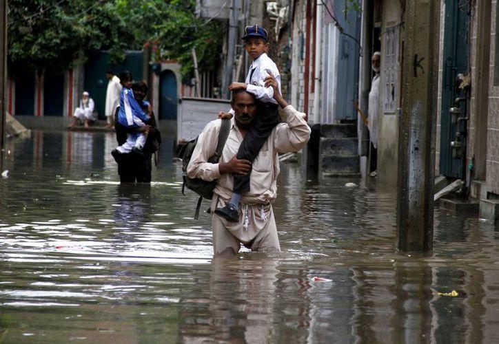 Un hombre camina por una de las zonas inundadas tras las lluvias registradas en Rawalpindi, en Pakistán. (EFE)