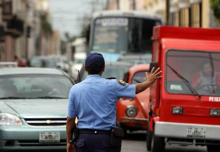 Agentes de la Policía Municipal deben de entrar 'al quite' para agilizar el tránsito de miles de vehículos que circulan en el centro de Mérida. (Milenio Novedades)