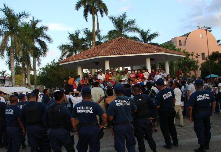 La turba enfurecida retuvo a Marcelino Cruz Canul y Justino Cen Dzul, en el parque principal de la ciudad.  (Manuel Salazar/SIPSE)
