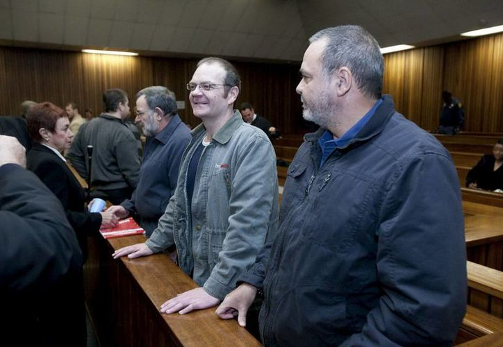 Los hermanos Andre (c) y Mike du Toit (der) asisten a su juicio en Pretoria, Sudáfrica acusados de planear el asesinato de Nelson Mandela. (Archivo/EFE)