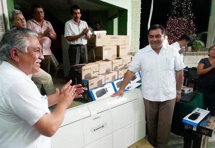 El dirigente del Stspeidy, Jervis Garcia Vázquez, recibe  cuatro equipos de aire acondicionado para el local de sus agremiados. (izq). (Milenio Novedades)