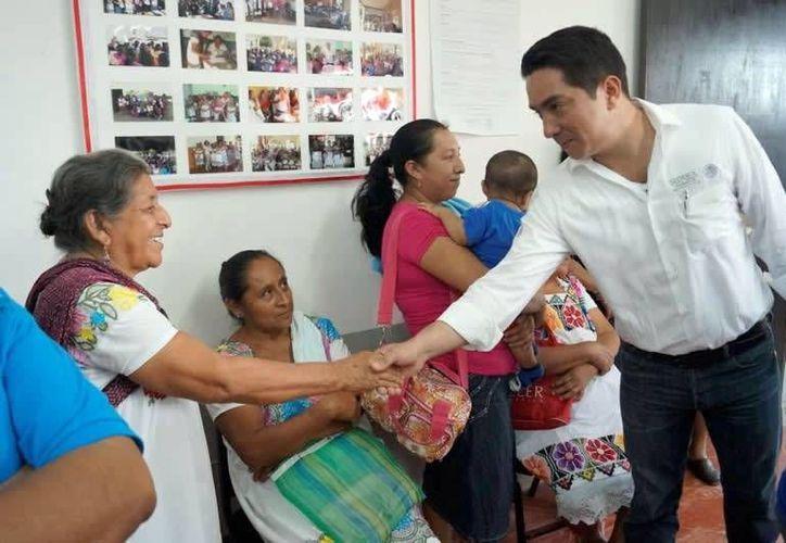 El delegado de la Sedesol, Luis Borjas Romero saluda a una de las beneficiarias. (Milenio Novedades)