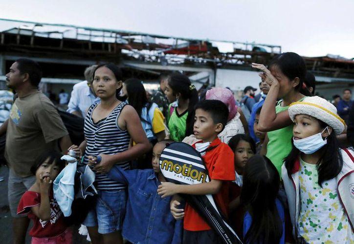Varios supervivientes esperan la llegada de un avión militar en el aeropuerto de Tacloban para volar a Manila, Filipinas. (EFE)