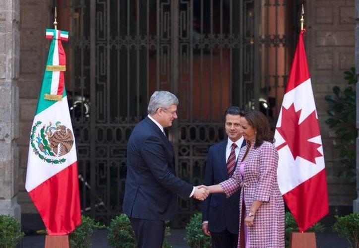 La secretaria de Turismo, Claudia Ruiz, saluda al primer ministro de Canadá, mientras el presidente Enrique Peña atestigua. (presidencia.gob.mx)