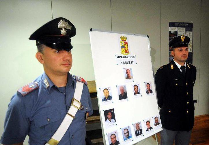 Dos agentes posan junto a las fotos de 11 sospechosos de pertenecer a la mafia italiana. (Agencias)