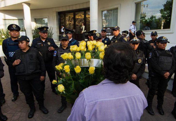 Una persona llega a la funeraria con rosas amarillas, las favoritas de García Márquez. (Notimex)