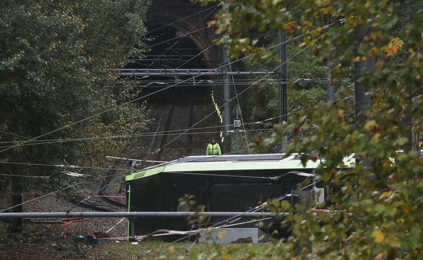 Un socorrista observa un tranvía descarrilado en Croydon, sur de Londres, este miércoles 9 de noviembre de 2016. El tranvía se descarriló antes del amanecer dejando decenas de heridos. (Steve Parsons/PA via AP)