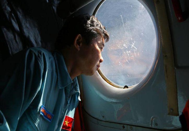 Lang Van Ngan, oficial de la Fuerza Aérea vietnamita, observa desde un avión el vuelo AN-26 que participa de la búsqueda del avión de Malaysia Airlines. (Agencias)