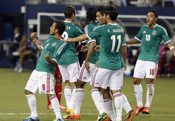 Luis Montes es felicitado tras anotar de palomita el gol del empate. Entonces todo era alegría. (Agencias)
