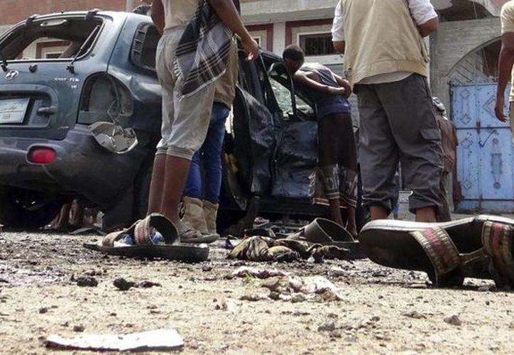Varias personas inspeccionan el lugar de un atentado suicida en la ciudad meriodional de Aden, Yemen, el 23 de mayo de 2016. (EFE)