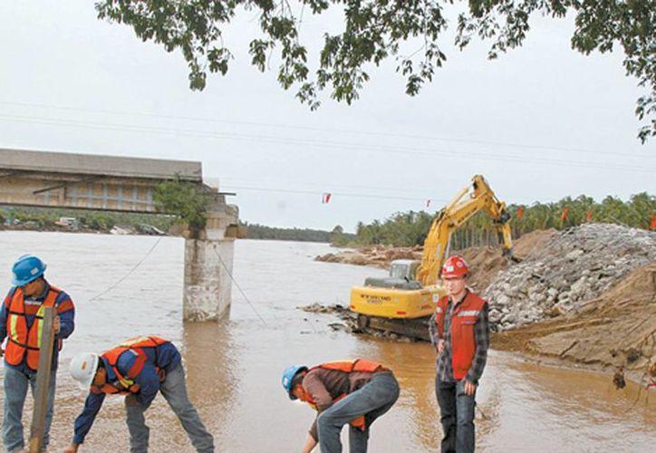 Reconstrucción de uno de los puentes afectados por los temporales Ingrid y Manuel. (Milenio)