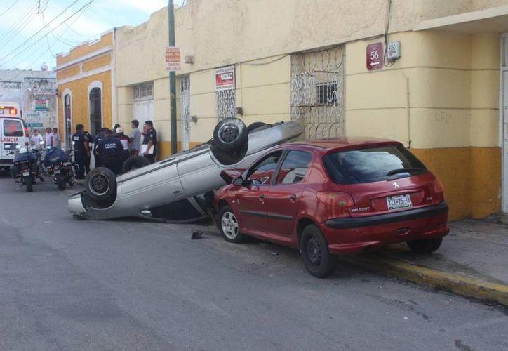 Tras chocar contra un Peugeot, un Nissan volcó en la calle 55 x 56 del centro de Mérida. (Fotos: cortesía de la PMM)