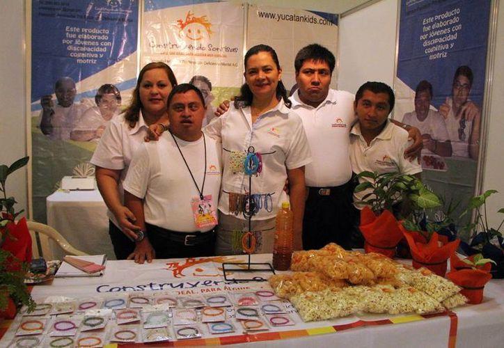 Jóvenes que atienden el módulo que la organización tiene en la Expo Comercio. (José Acosta/SIPSE)