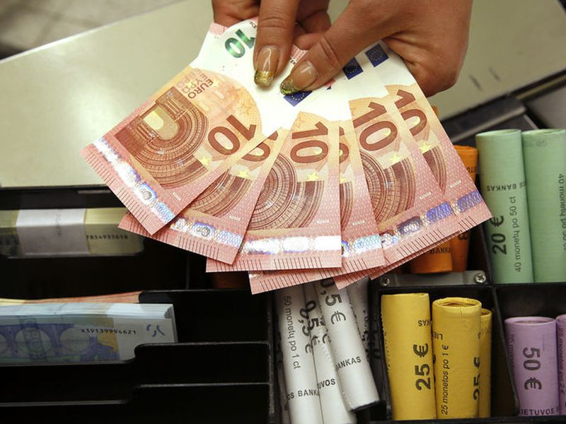 Euro coins and banknotes are shown by a salesclerk at a shop in Vilnius, Lithuania. Italy's economy minister says the new populist government isn't discussing any proposal to leave the eurozone.