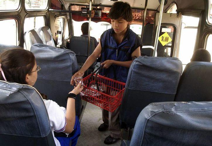 Un niño trabaja vendiendo dulces y maní en un autobús. (Archivo/EFE)