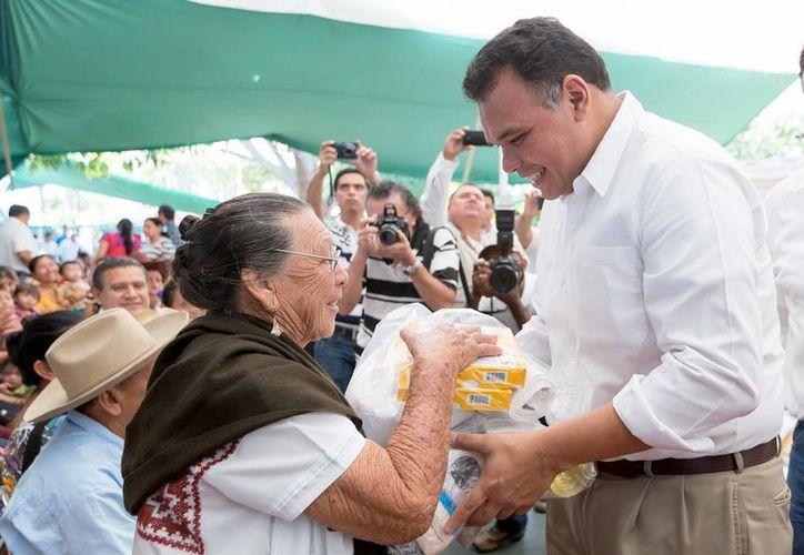 A los habitantes de Tekit les correspondió material para la confección de ropa. En la imagen el Gobernador de Yucatán le entrega la materia prima a una mujer del lugar. (Milenio Novedades)